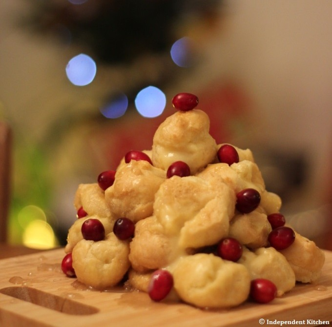Christmas croquembouche decorated with fresh cranberries drizzled with caramel