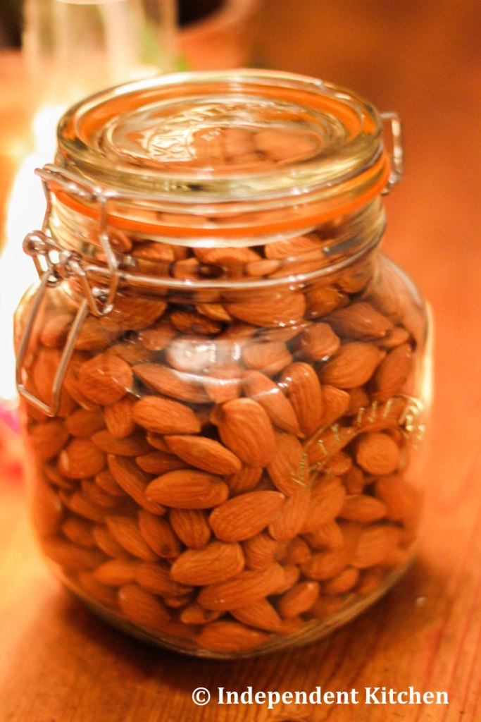 A jar of raw hulled almonds, ready to be blended in a Vitamix to make raw vegan almond butter
