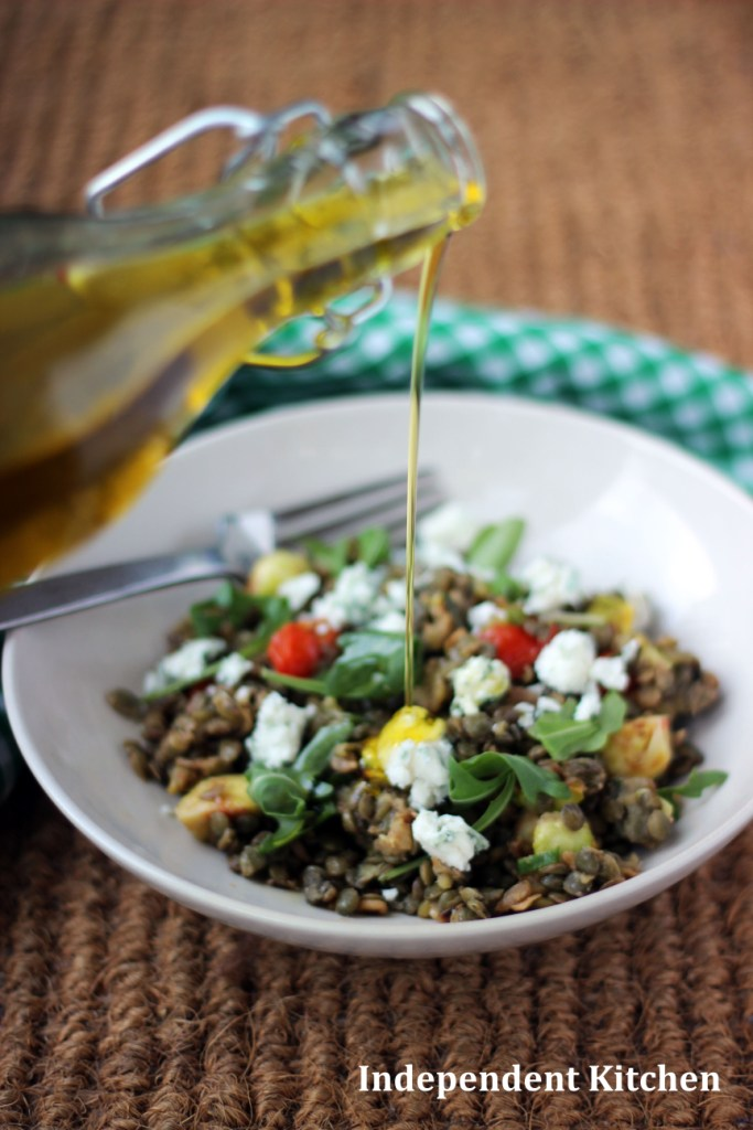 Olive oil drizzled over smoked eggplant and puy lentil salad
